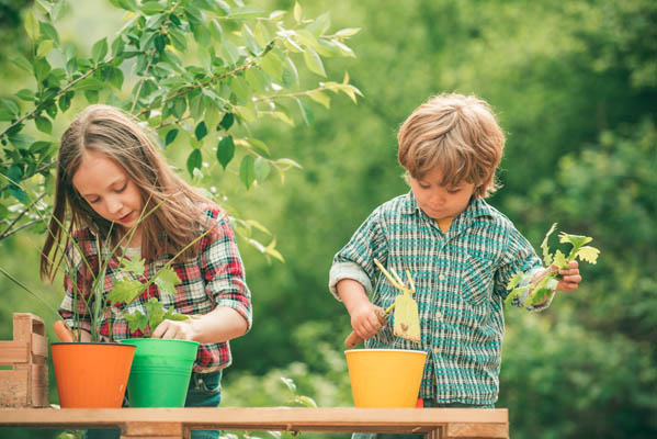 Planting flowers in pot. Carefree childhood. Shovel Planting flowers. American kids on farm.